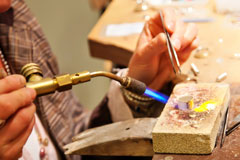 jeweler using a soldering torch and tweezers
