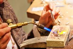 jeweler using a soldering torch and tweezers